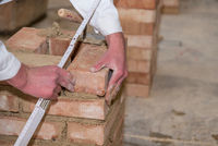 Mason walls brick wall with the help of a trowel and folding rule - close-up