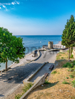 A beautiful street and the beach in Nessebar ancient city on the Bulgarian Black Sea Coast. Nesebar or Nesebr is a UNESCO World Heritage Site. A street in Nessebar on a sunny day with blue sky