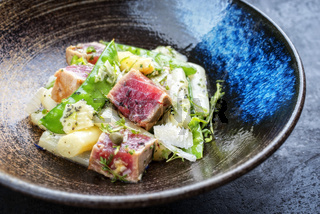 Modern fried tuna fish tataki filet salad with white asparagus sugar snaps and parmesan cheese as top view on a plate