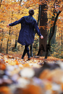 rear view of woman enjoying autumn walk in forest