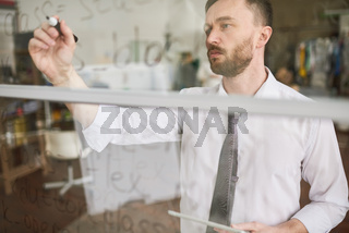 Handsome Man Writing on Glass Wall in Office