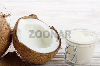 Background of coconut, coconut shell, hard oil in airtight glass jar on white wooden table