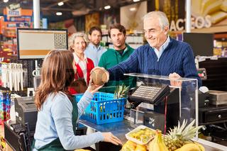 Kunde beim Bezahlen an der Supermarkt Kasse