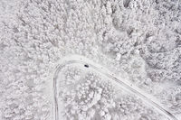 Car on road in winter trough a forest covered with snow. Aerial photography of a road in wintertime trough a forest covered in snow. High mountain pass.