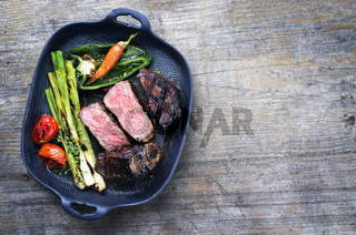 Barbecue dry aged wagyu roast beef steak with vegetable and herbs as top view on a gray cast iron pan with copy space right