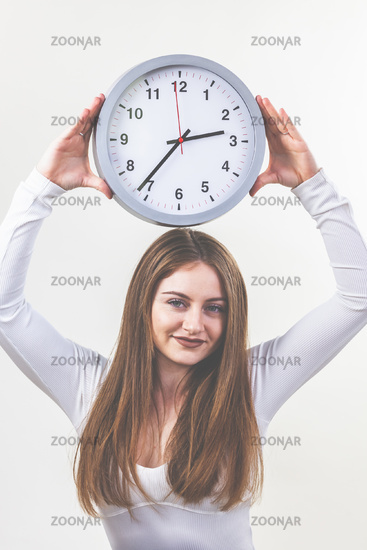 Woman, white shirt and jeans, brunette, long hair, holding a clock in her hands. Appointment, Punctu