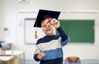 little boy in mortarboard looking through diploma