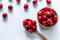Red ripe cherries with wooden spoon on white background. Flat lay. Food concept.
