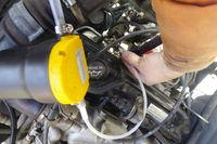 Mechanic changing oil through the dipstick pump