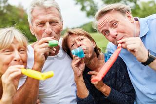 Senioren mit Tröten feiern eine Party