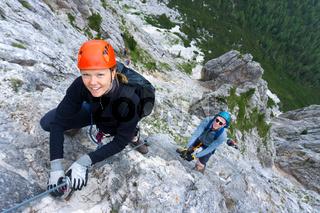 man and woman in their twenties climb a steep Via Ferrata for fun during their holidays