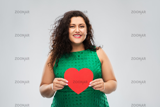happy woman in green dress holding red heart