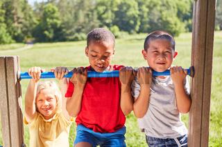 Kinder machen Klimmzug an einem Klettergerüst