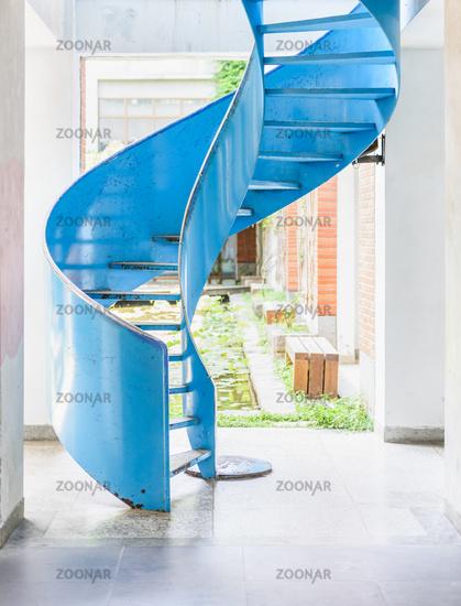 Blue metal spiral ladder in bright room