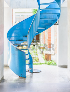 Blue metal spiral ladder in bright room