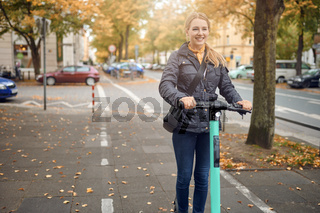 Junge Frau fährt mit einem Elektroroller