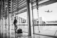 Young woman waiting at airport, looking through the gate window.