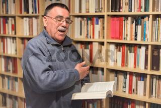 Portrait of senior man reading book in the hand on bookshelf background