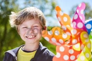 Frech lächelnder Junge mit einem Windrad