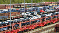 lots of new cars loaded on railway autorack wagons ready for shipment
