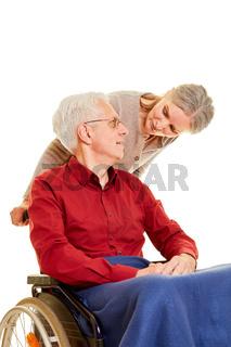 Seniorin schiebt Mann im Rollstuhl
