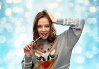 woman in christmas sweater biting candy cane