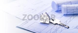 Schlüssel mit Haus als Schlüsselanhänger auf Bauplänen