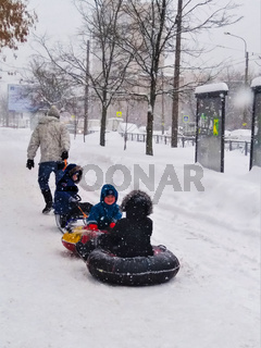 A father carries his three children on a steam train of sledges and two airbags along a snowy winter street in a snowstorm.