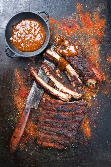 Barbecue spare ribs St Louis cut with hot rub and BBQ sauce as closeup on a black board