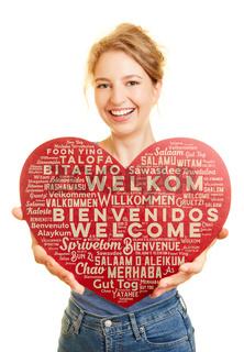 Frau zeigt Herz mit Willkommen Gruß in vielen Sprachen