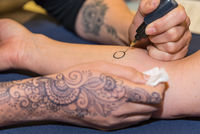 Person makes henna tattoo on his arm - Mehndi
