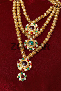 Multi layered artificial golden rani haar jewelry on a red background.