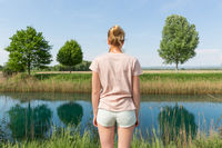Young woman wearing casual summer clothes enjoying beautiful view of peaceful countryside.