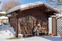 Snow-covered wooden hut in the garden - gazebo in winter landscape