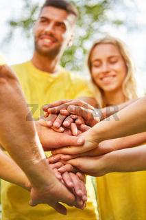 Junge Leute stapeln Hände im Teambuilding Workshop