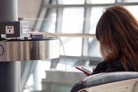 A young woman sitting at a charging station and looking at her smartphone