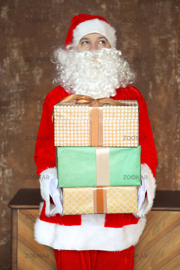 Santa Claus secretly putting gift boxes under the Christmas tree