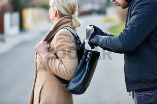 Mann als Dieb beim Stehlen aus Tasche