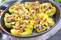 Pepper stuffed with vegetables in pan on black wooden board