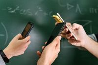 Students using mobile phones in classroom with a chalkboard in the background.
