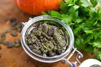 Home made pumpkin seeds pesto sauce with walnuts, olive oil, salt, greens and spices in a jar, vegan, vegetarian healthy food concept.