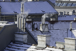 Smoking chmineys in a sowy urban winter scene in Vienna/ Austria. Heating energy and environmental pollution concept.