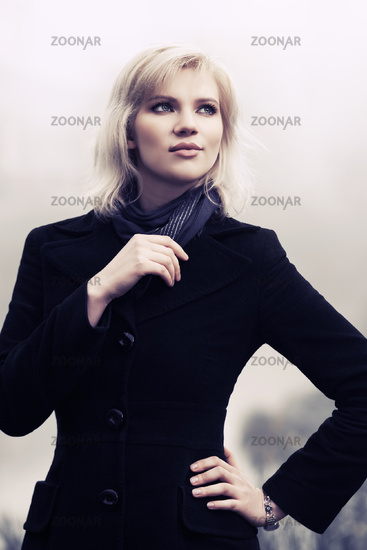 Young fashion woman in black coat walking in a fog outdoor