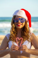 Woman holding candy canes to the shape of a heart on the beach in Australia