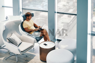 Beautiful young woman working on laptop while sitting in a big comfortable chair at modern interior