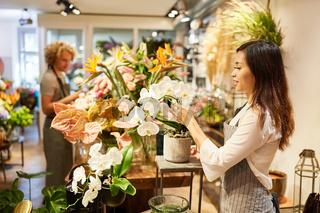 Asiatische Frau als Floristin dekoriert Blumengebinde