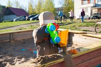 A little boy of three years old is playing on a cool spring sunny day in the sandbox in the city yard with his toy truck