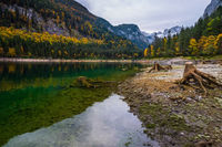 Vorderer Gosausee lake, Upper Austria. Colorful autumn alpine view of mountain lake with clear transparent water and reflections. Dachstein summit and glacier in far.