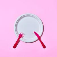 Dining set served fork and knife on pink.