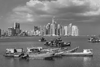 old wooden fishing boats in front of the skyline of panama city panama in black and white